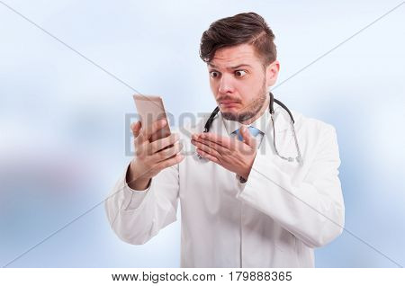 Young Medic Looking Perplexed At His Phone