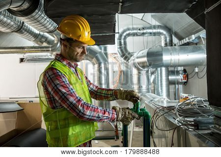 Worker making final touches to HVAC system. HVAC system stands for heating ventilation and air conditioning technology. Team work HVAC indoor environmental comfort concept photo.