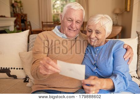 Content senior couple looking at an old photograph of themselves when they were young while sitting on their living room sofa at home