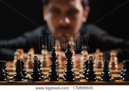 Portrait of adult man who is participating in chess game. Focus on chess figures