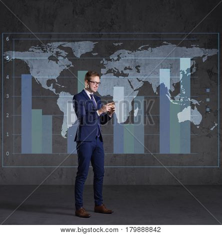 Businessman with smartphone standing over diagram. World map background. Business, globalization, capitalism concept.