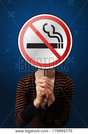 Casual young woman holding round sign with no smoking graphic