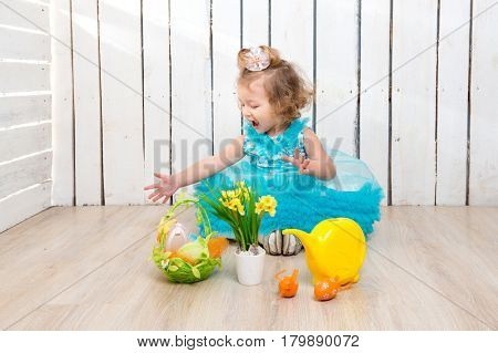 beautiful little girl in blue dress on the floor playing with easter decorations