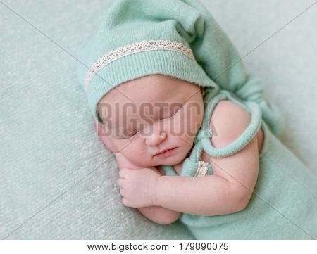Cute girl sleeping on her side in green hat, wearing green small outfit, closeup