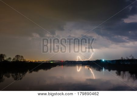 Summer night landscape, rain and lightning above the river