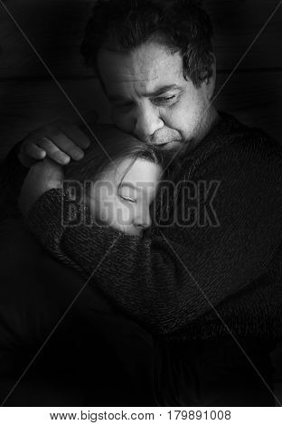 Black and white portrait. Parting. Sad father hugs his teen daughter