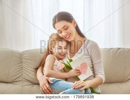 Happy mother's day! Child daughter congratulates mom and gives her flowers tulips and postcard. Mum and girl smiling and hugging. Family holiday and togetherness.