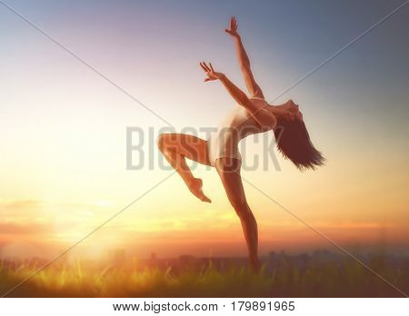Young beautiful woman is dancing on sunset background outdoors. Concept of freedom and unity with nature.