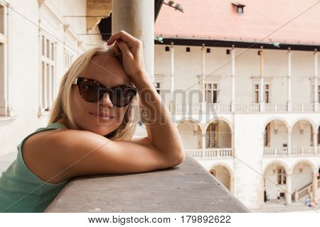 Female traveler on the background of Arcades in Wawel Castle in Cracow. Poland. Renaissance.