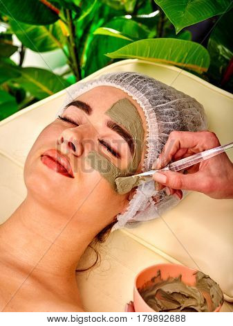 Mud facial mask of woman in spa salon. Massage with clay full face. Girl wearing medical hat on with therapy room. Female lying wooden spa bed. Beautician with brush therapeutic procedure green plant
