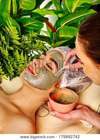 Mud facial mask of woman in spa salon. Massage with clay full face in therapy room. Female lying wooden spa bed. Applying beautician with bowl therapeutic procedure on green plants background.