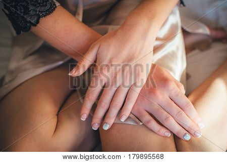 Morning of young beautiful woman - bride, with her hands crossed. Female fingernails with french manicure. Getting ready for wedding ceremony. Horizontal color image. The Nail Design. Beautiful wedding french manicure for the bride in gentle tones.