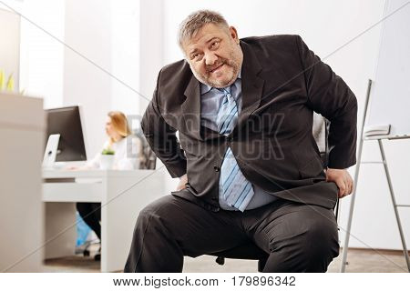 My knees hurt. Helpless overweight middle aged man feeling unable standing up after working long hours sitting at the desk