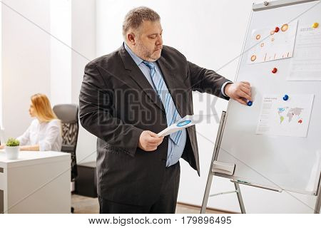 Put it in its place. Engaged attentive hardworking man making information looking more comprehensive for him while analyzing recent sales data