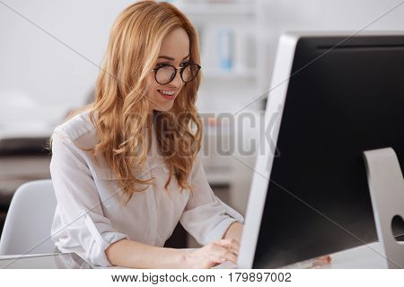 Full of positive emotions. Involved glad young manager sitting at the table in the office and working while using computer and typing