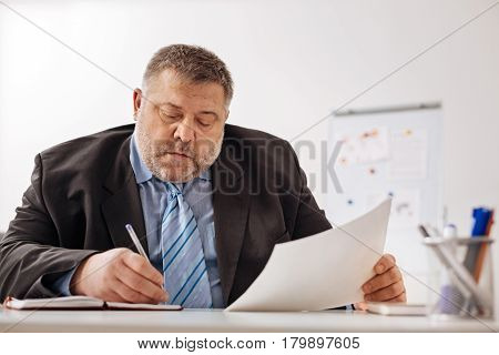 Fully concentrated. Chubby engaged white collar employee looking focused while doing his job on providing a sales report analysis