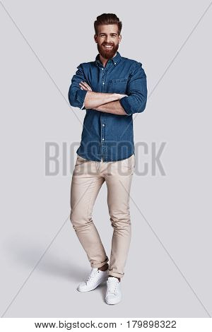 Confident in his style. Full length of handsome young man looking at camera and keeping arms crossed while standing against grey background