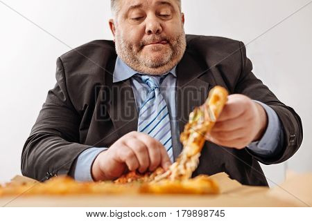 One more piece. Middle aged obese company employee ripping off a slice of pizza he usually ordering in the office while having a break from work