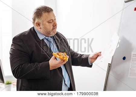 Busy throughout the day. Diligent engaged ambitious expert eating a slice of pizza while standing at the pin board and reading the report