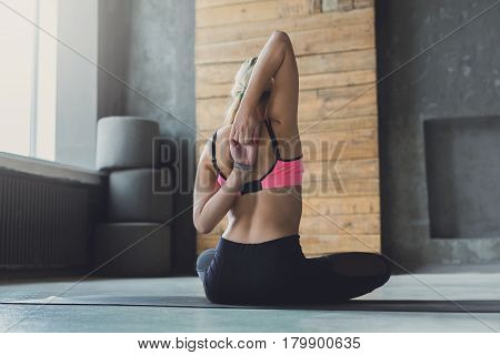 Woman sits and stretch hands behind back at yoga class,   gomukhasana exercise. Rear view of flexible yogi girl practicing yoga or pilates, sitting in cow face pose in fitness studio