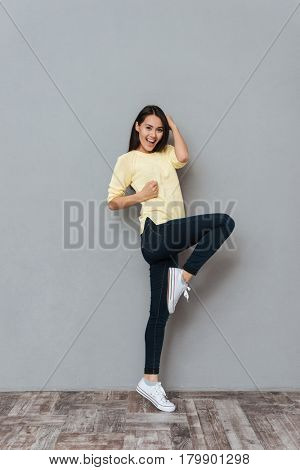 Full length of happy lovely young woman standing and having fun over grey background