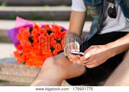 Waiting for you. Young man typing message on the mobile phone while sitting on the staircase with bouquet of roses laying near him