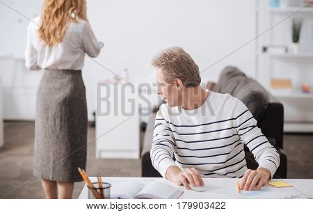 Sexual harassment at work. Optimistic lively mature businessman sitting in the office and working on the project while flirting and staring at secretary