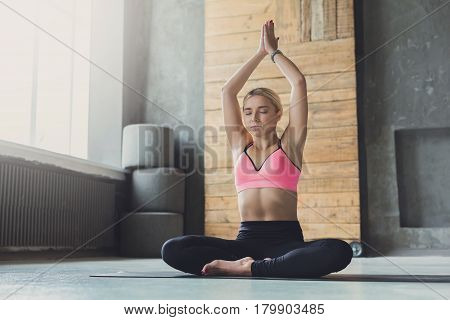 Woman practicing yoga in lotus pose indoor. Fit girl in sportswear sitting in Padmasana exercise, meditation session in the morning at fitness studio, full length