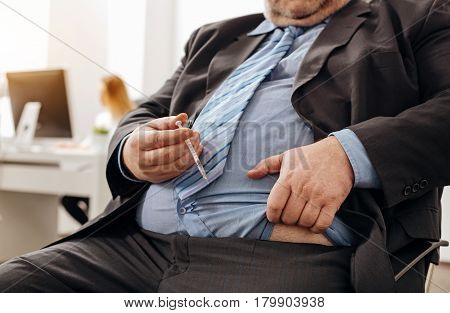 Needed remedy. Scrupulous pudgy unhealthy man doing an injection at his workplace because of not eating healthy and having excess weight