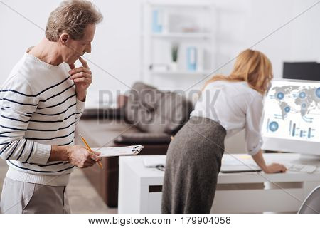 Expressing inappropriate thoughts. Thoughtful cheerful involved office manager standing in the business center and performing responsibilities while looking attentively at young coworker back