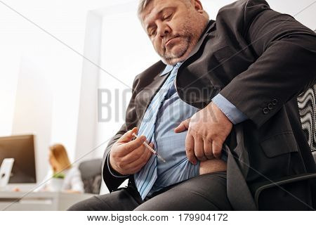 Diabetic burden. Stout upset middle aged man experiencing some health issues which his excess weight causing him
