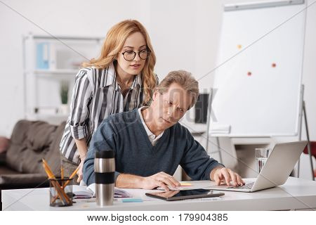 Full of charm . Beautiful interested involved woman standing in the office next to colleague while working and flirting