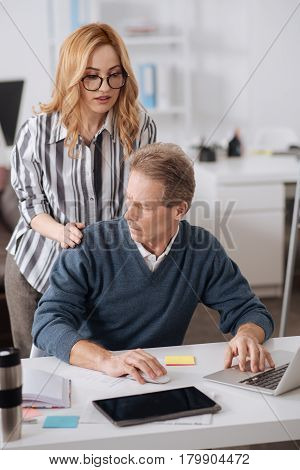 Showing my feelings to you . Charismatic interested involved businesswoman standing in the office next to the colleague while working and flirting