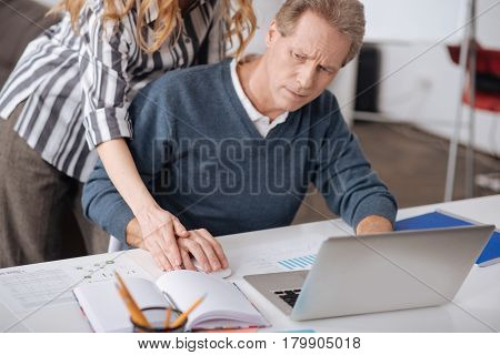 Full of disturbance. Angry involved mature office manager sitting in the office while working and expressing negativity towards colleagues behavior