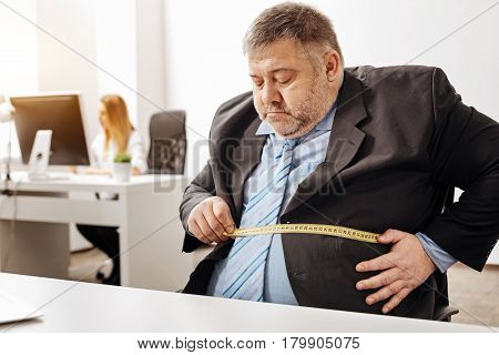 Not looking good. Hilarious but sad obese guy taking some measurements of his belly while sitting at his workplace