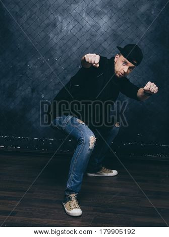 Dancer on grunge wall background. The guy is dressed in stylish clothes. Paphos photos.