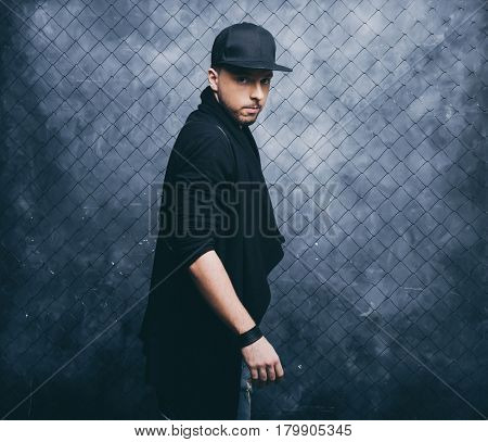 The guy in stylish clothes. Dancer on grunge wall background.
