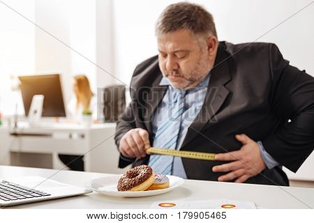 Did I loose some pounds. Excessive amusing overweight man using a measuring tape for estimating his weight while having a plate of doughnuts standing in front of him