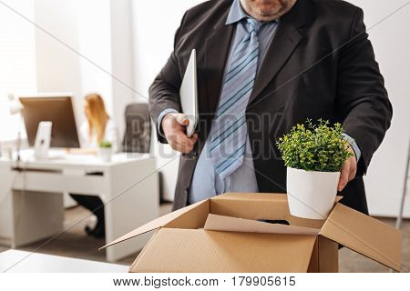 Fulfilling last task. Troubled sad puffy man being fired and packing his stuff in a box before leaving his workplace