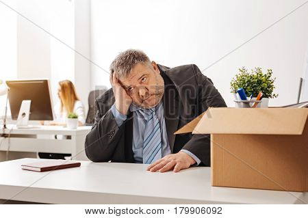 My wife is gonna kill me. Sad emotional chubby employee looking hopeless while sitting at his workplace after being fired