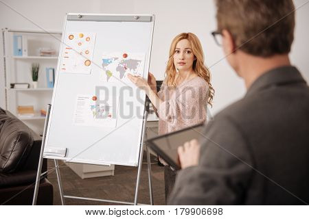 Representing my work. Intelligent shy professional office manager standing in front of the whiteboard in the office and representing the project in front of the boss while working