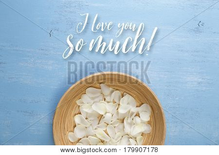 Petals of white roses on blue painted rustic background. Fresh natural flowers in bowl. I love you so much.