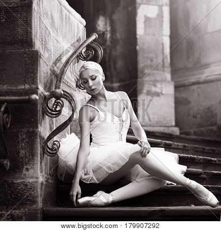Graceful beauty. Monochrome shot of a young ballerina posing on stone stairs