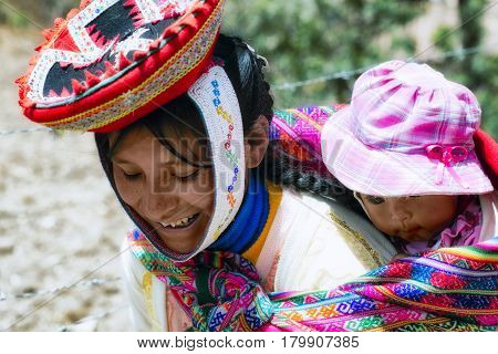 Close up of portrait of a smiling Quechua woman dressed in colourful traditional handmade outfit and carrying her baby in a sling. October 21 2012 - Patachancha Cuzco Peru