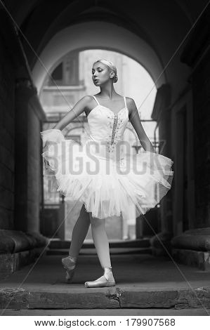 Can you be more graceful Monochrome shot of an elegant female ballet dancer posing in an archway soft focus