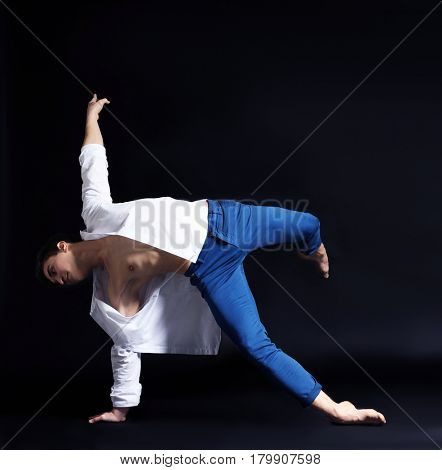 Handsome young ballet dancer on dark background