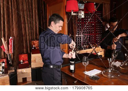 Man opening bottle of red wine