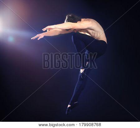 Handsome young ballet dancer on dark background