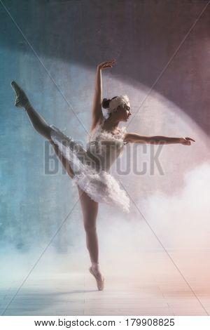 Young beautiful ballerina dancing in studio with smoke effect