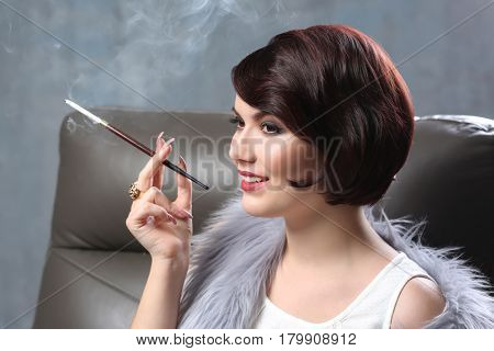 Young woman sitting in armchair and smoking with cigarette holder on color background